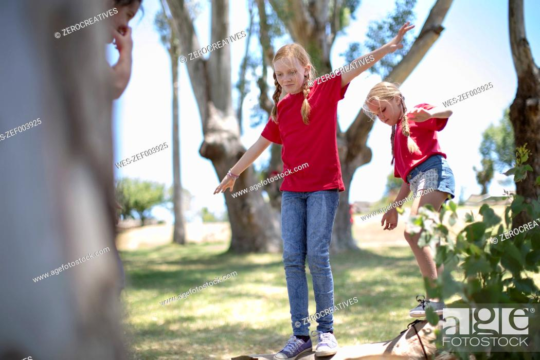 Stock Photo: South Africa, Kids on field trip balancing on tree trunk.