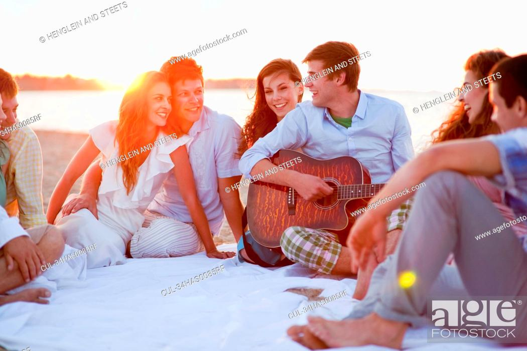 Imagen: Man playing music for friends on beach.