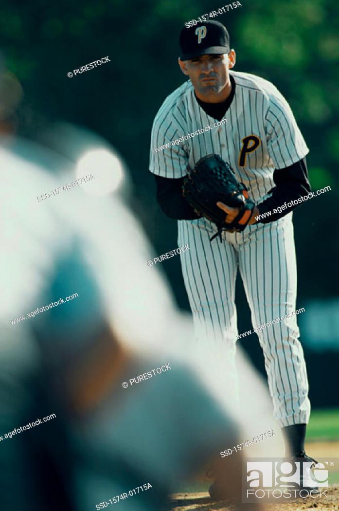Stock Photo: Portrait of a baseball pitcher bending forward.