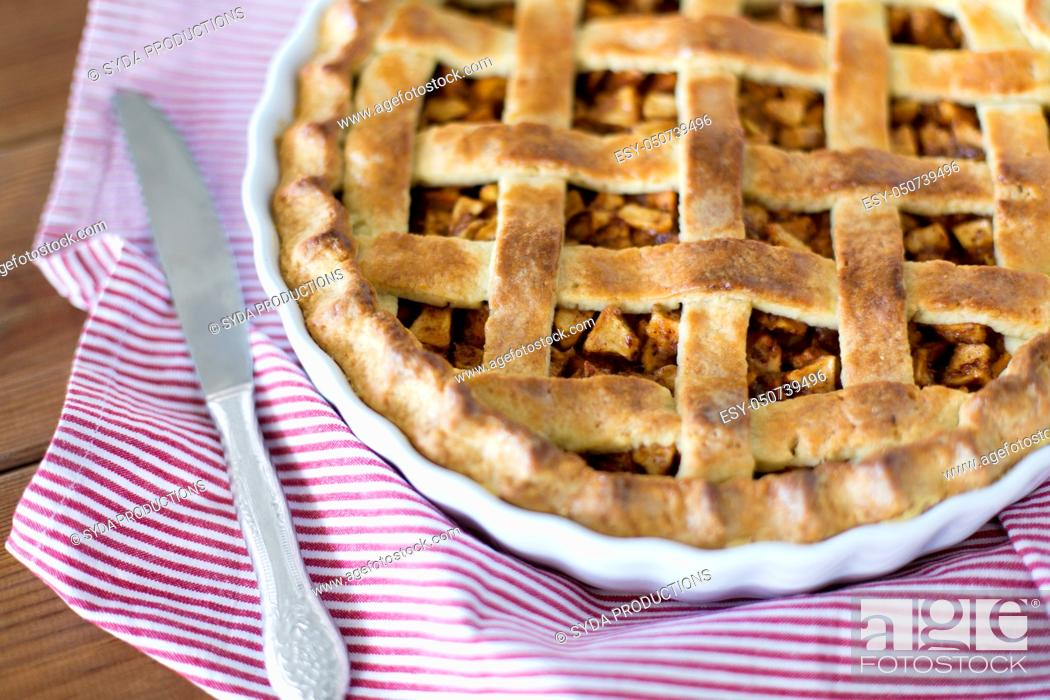 Stock Photo: close up of apple pie in baking mold and knife.