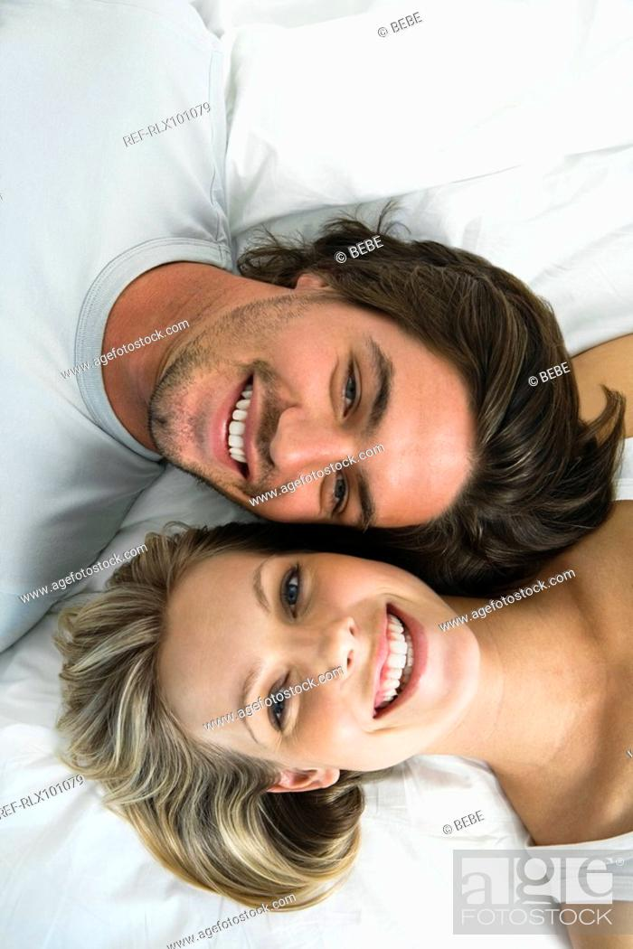 Stock Photo: Young woman an man lying in bed, smiling, portrait.