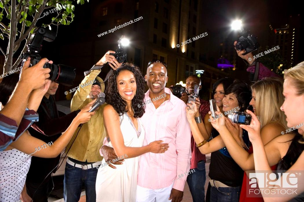 Stock Photo: Young couple arm in arm surrounded in paparazzi, smiling.