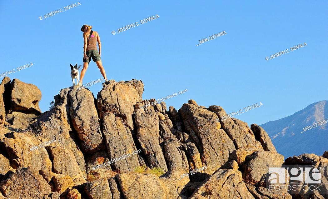 Stock Photo: Woman climbing rocks with dog, Alabama Hills, California, USA.