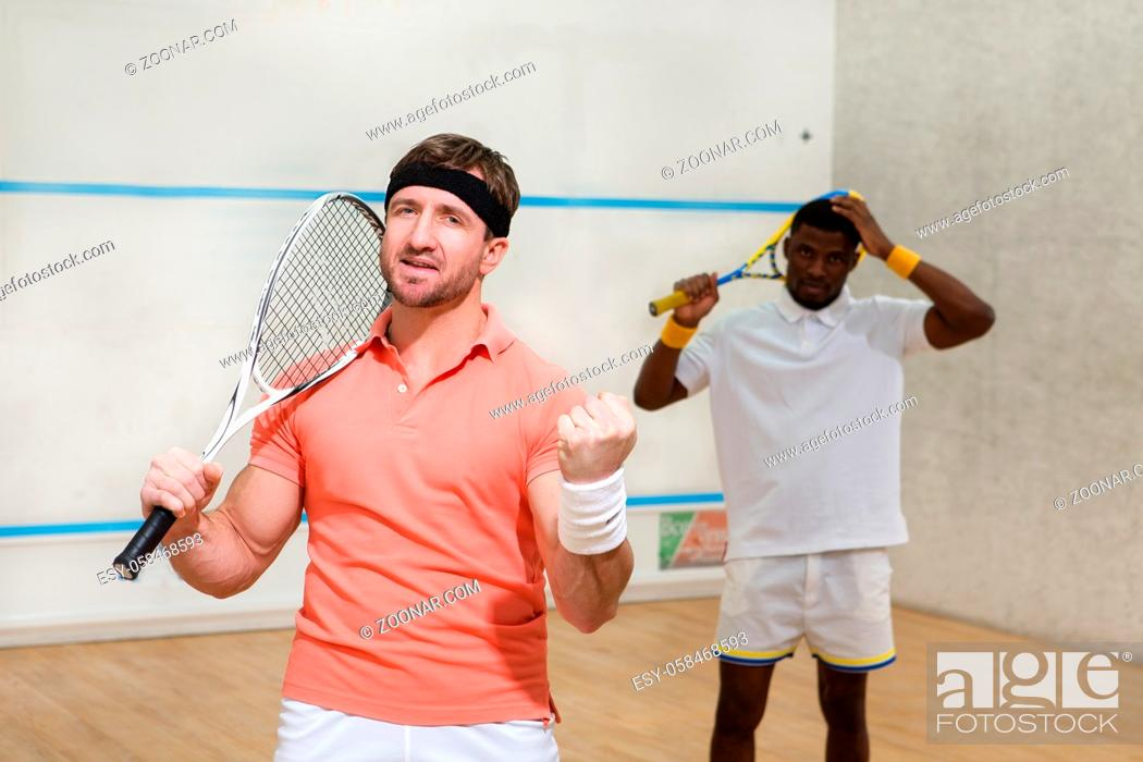 Stock Photo: Handsome men playing squash on court and expressing positive emotions during game: excitedness, astonishmen.