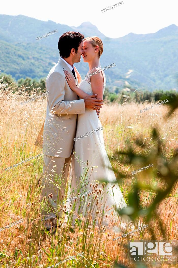 Stock Photo: Newlyweds embracing in field.