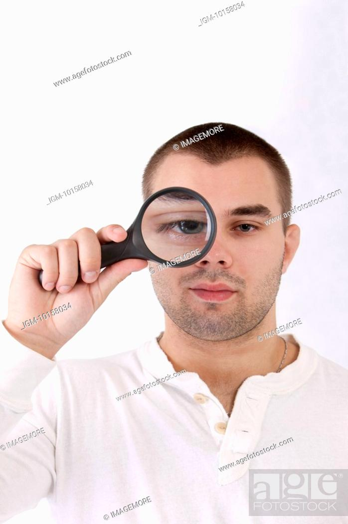 Stock Photo: Young man putting a magnifying glass on one eye.