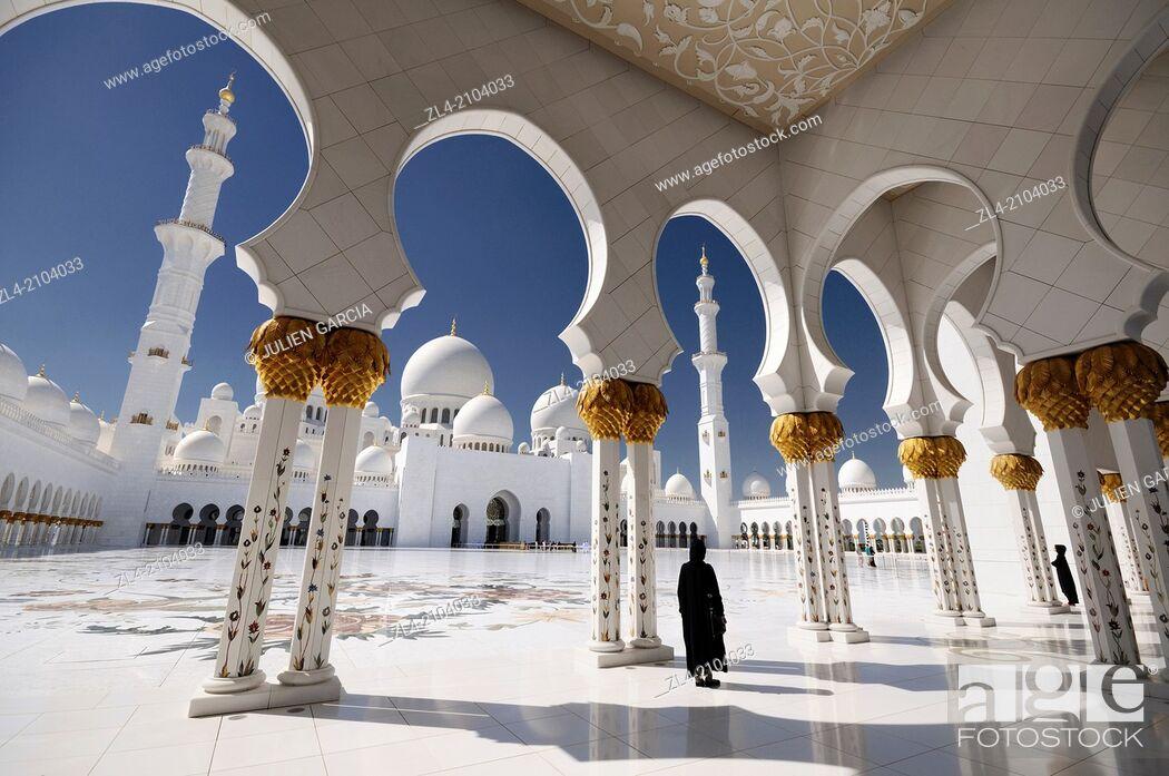 Stock Photo: Woman wearing an abaya in the mosque courtyard. United Arab Emirates, UAE, Abu Dhabi, Sheikh Zayed Grand Mosque.
