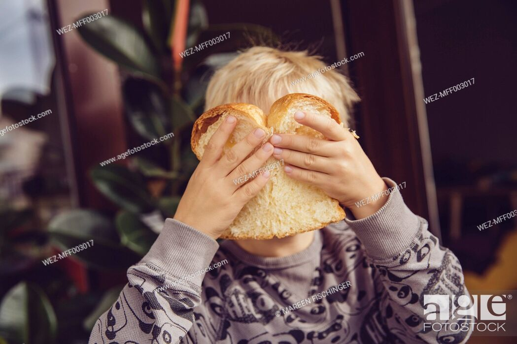 Stock Photo: Little boy covering his face with a slice of white bread.