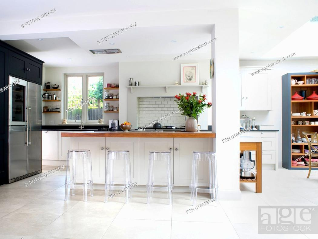 Perspex stools at breakfast bar in large modern white kitchen ...