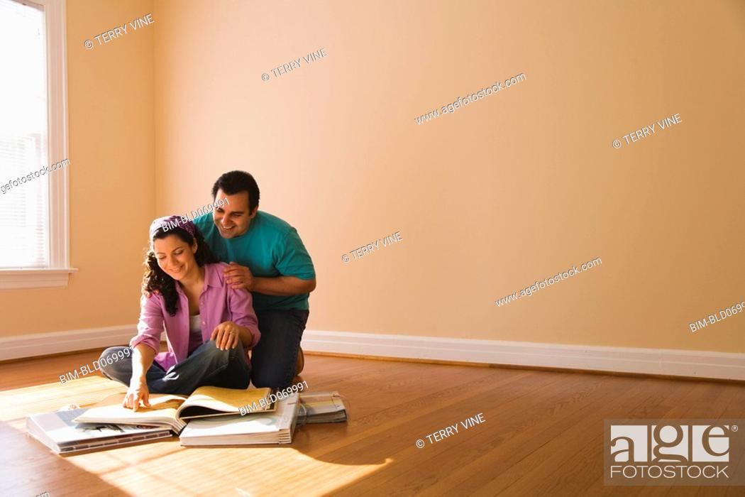 Stock Photo: Hispanic couple looking at textile swatches in new home.