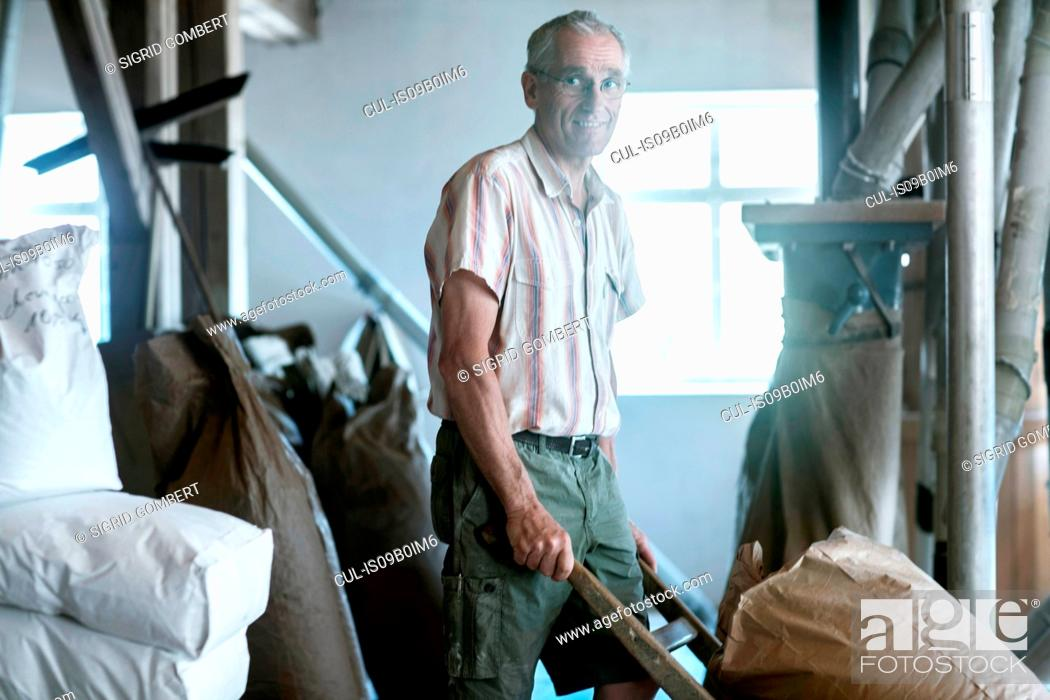 Stock Photo: Male miller pushing sack barrow at wheat mill.
