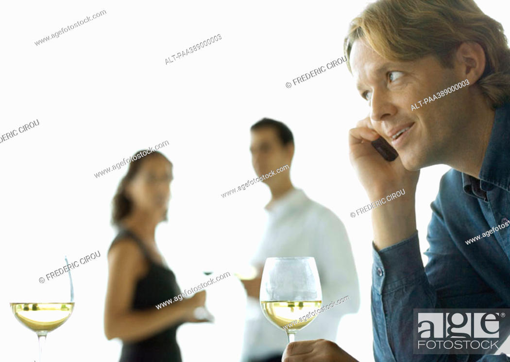 Stock Photo: Man using cell phone, people drinking wine in background.