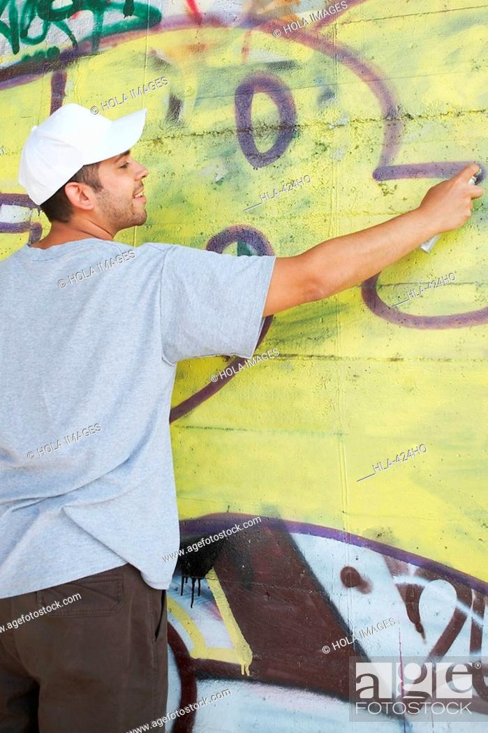 Imagen: Rear view of a young man making a graffiti on a wall.