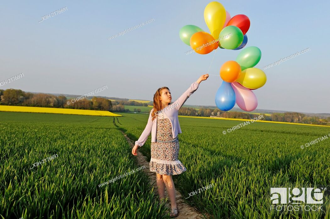 Stock Photo: little girl playing with balloons in the fields, Eure-et-Loir department, Centre region, France, Europe.