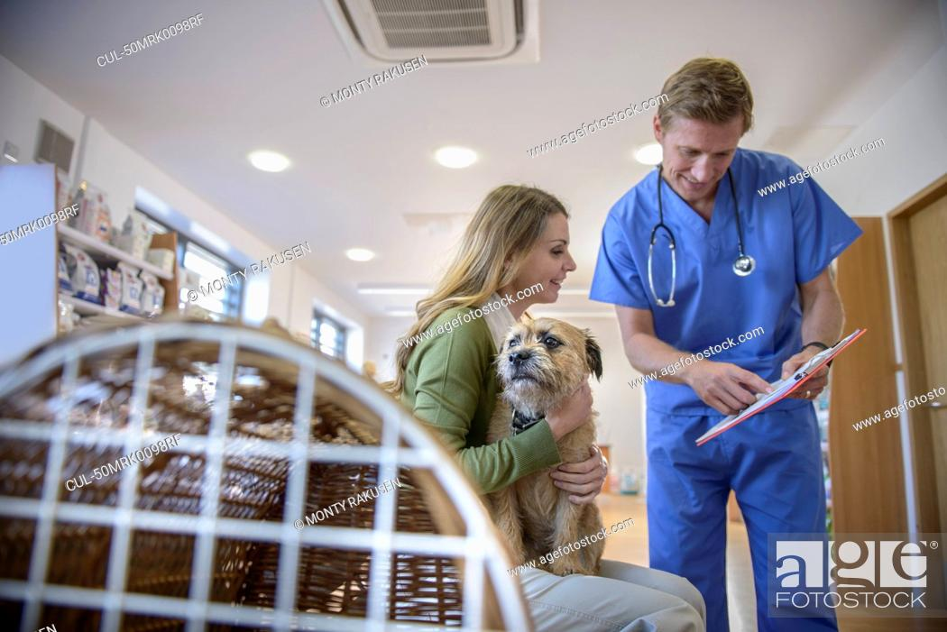 Stock Photo: Veterinarian talking to dog owner.
