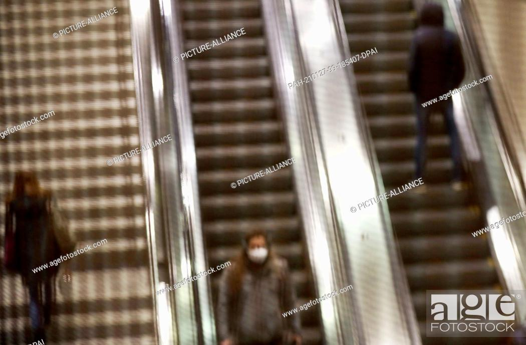 Imagen: 27 January 2021, North Rhine-Westphalia, Cologne: People ride behind a grid on an escalator. Chancellor Merkel and the heads of state governments have agreed to.