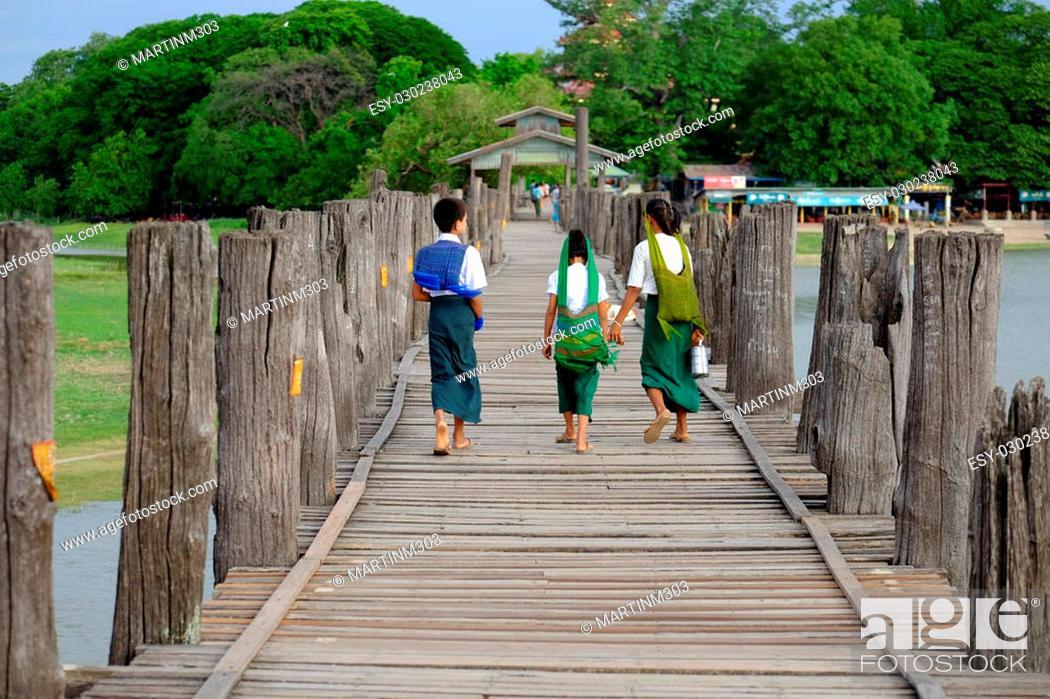 Stock Photo: Amarapura, Myanmar - 28 June, 2015: Children in colorful clothes walk to school on U Bein bridge in Amarapura, Myanmar.