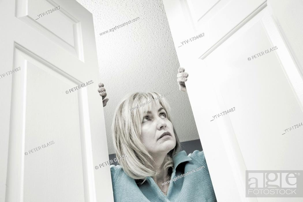 Stock Photo: Middle-age blond woman looking out through double doors.