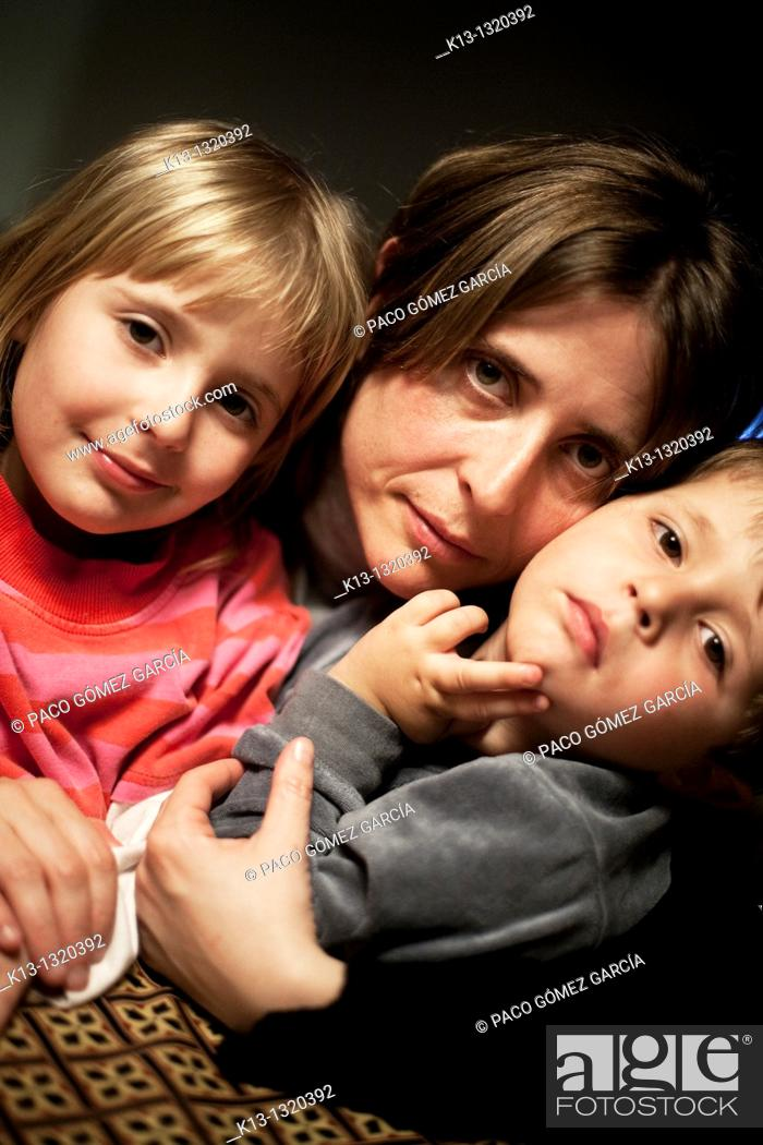 Stock Photo: Mother and two children, ages 4 and 6, smiling into camera.
