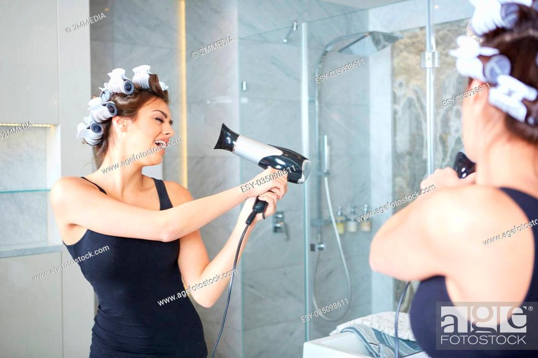Stock Photo: young woman putting curlers in her hair.
