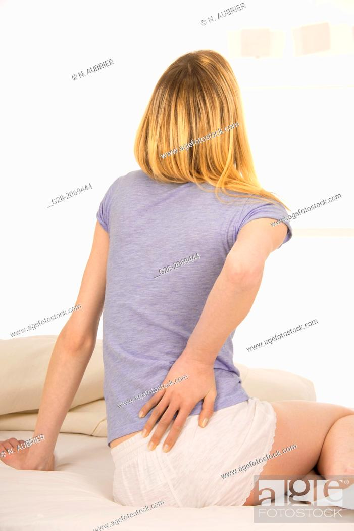 Stock Photo: Young beautiful woman sitting on a bed and suffering from back ache.