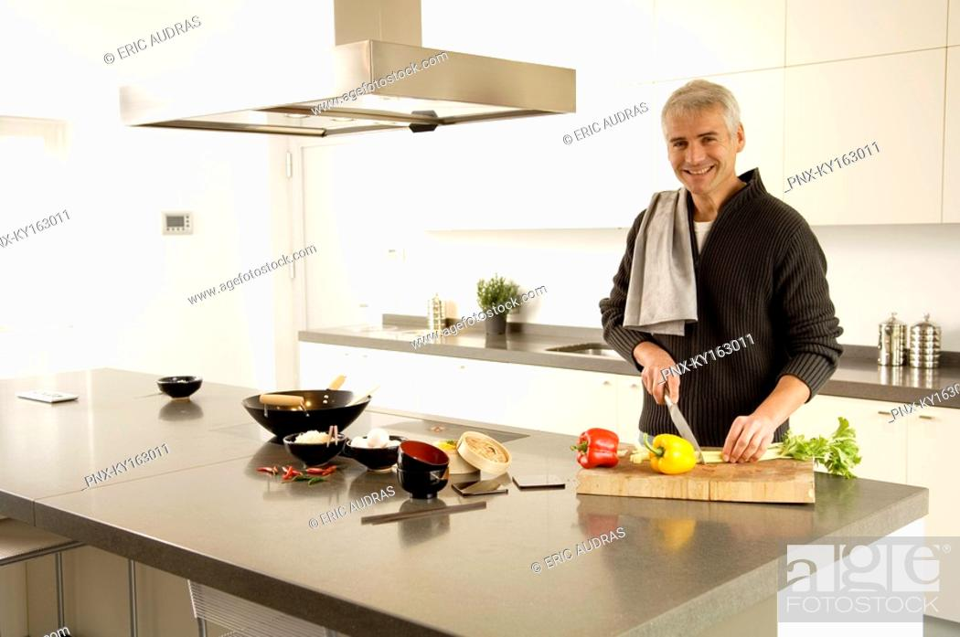 Stock Photo: Portrait of a mature man chopping vegetables in the kitchen.
