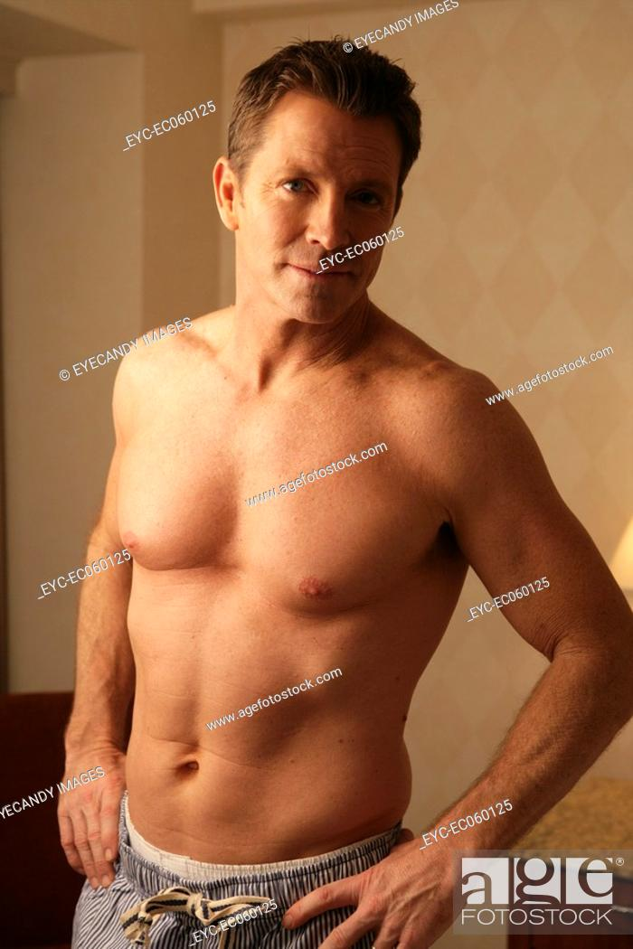 Stock Photo: Mature man looking at camera shirtless.