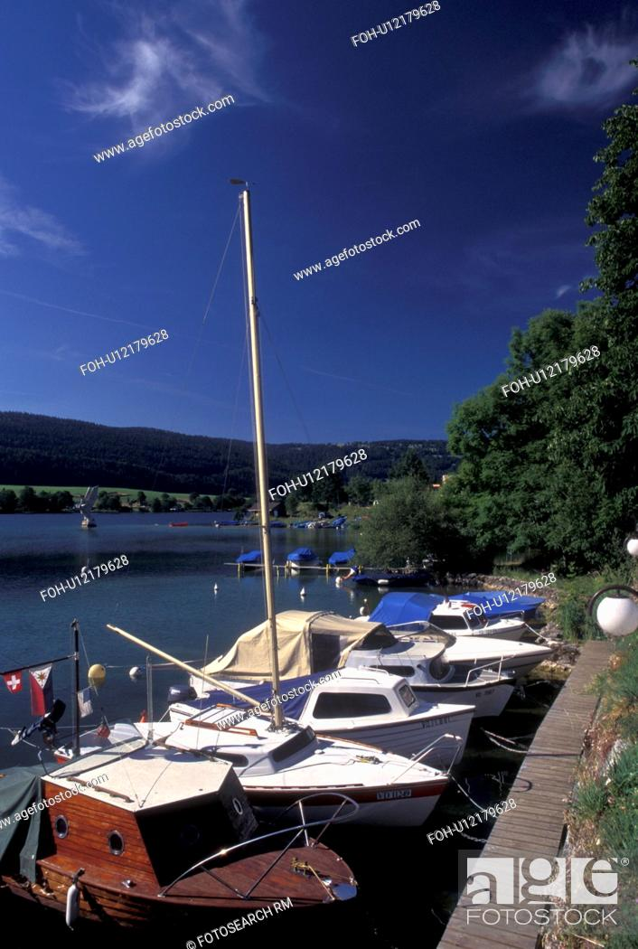 Stock Photo: Vallee de Joux, Switzerland, Vaud, Boats docked along the lakefront of Lac de Joux in Le Pont in the Jura mountain region.