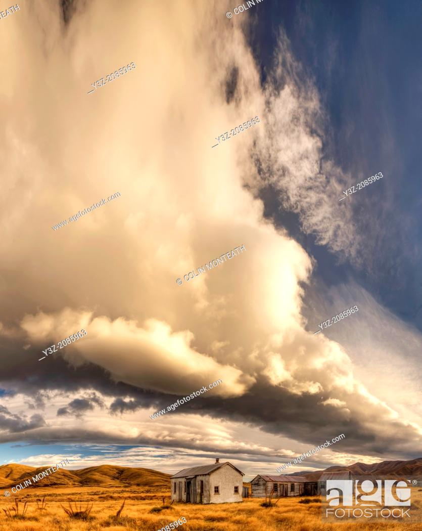 Stock Photo: Dawn lights up cloudscape over historic (1939) farm buildings near St Bathans, Central Otago, New Zealand.