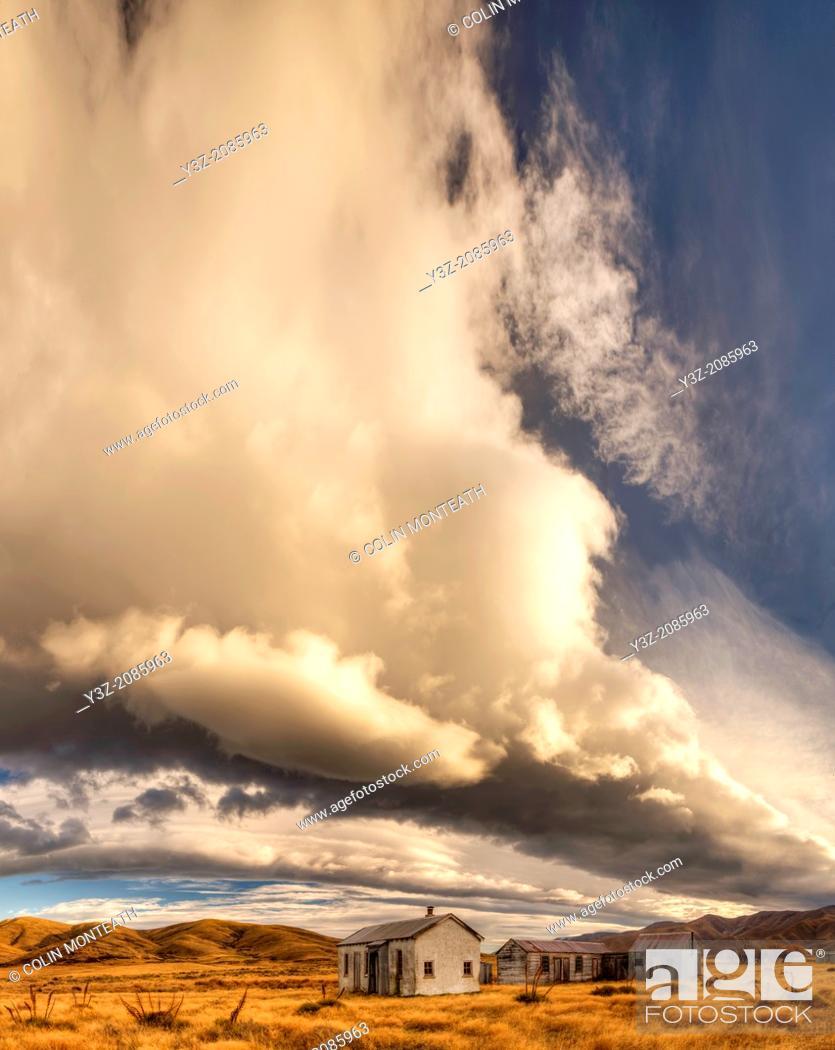 Imagen: Dawn lights up cloudscape over historic (1939) farm buildings near St Bathans, Central Otago, New Zealand.