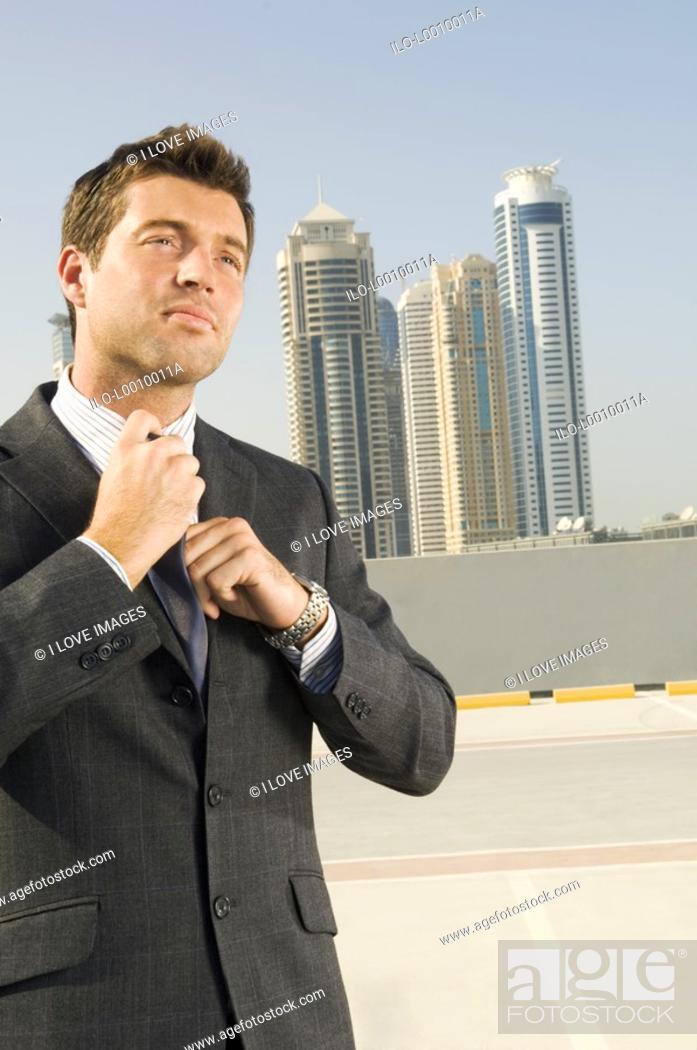 Stock Photo: A businessman adjusting his tie.