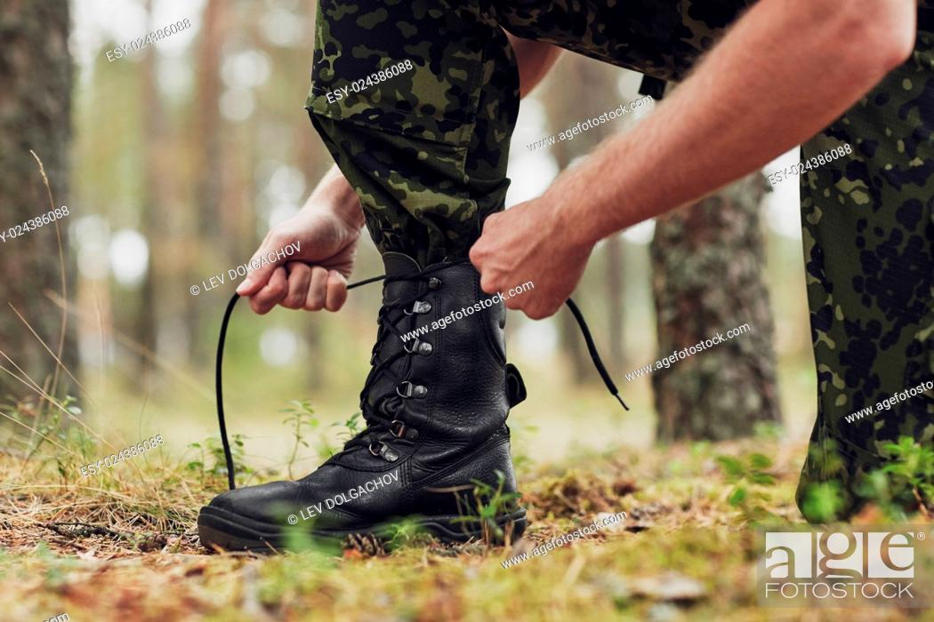 Stock Photo: war, hiking, army and people concept - close up of soldier boots and hands tying bootlaces in forest.