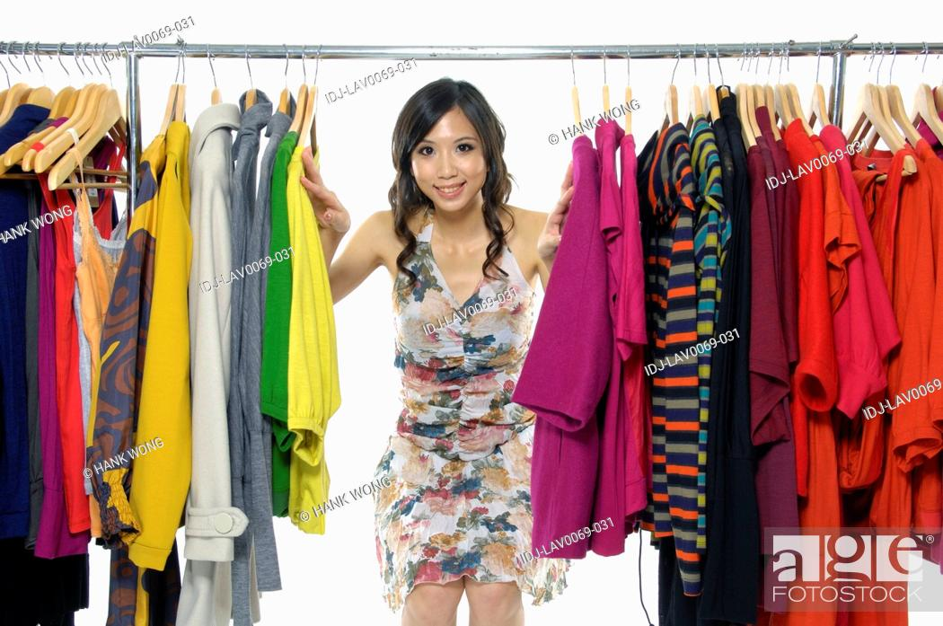 Stock Photo: Woman peeking through clothes in a clothing store.