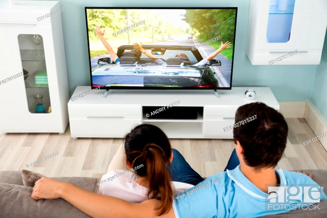 Stock Photo: Young Couple On Sofa Watching Movie On Television Together At Home.