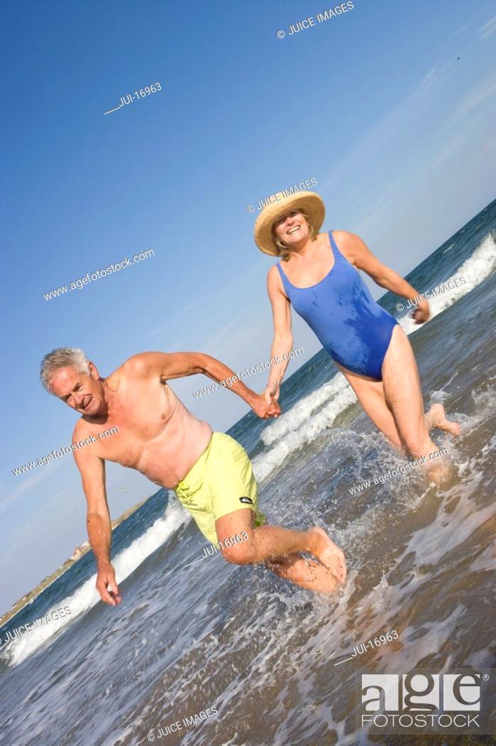 Stock Photo: Senior couple walking in sea.