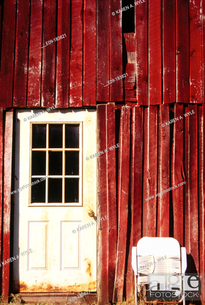 Stock Photo: Red-brown side of barn with white painted door and folded white lawn chair, Unionville, Indiana, USA.