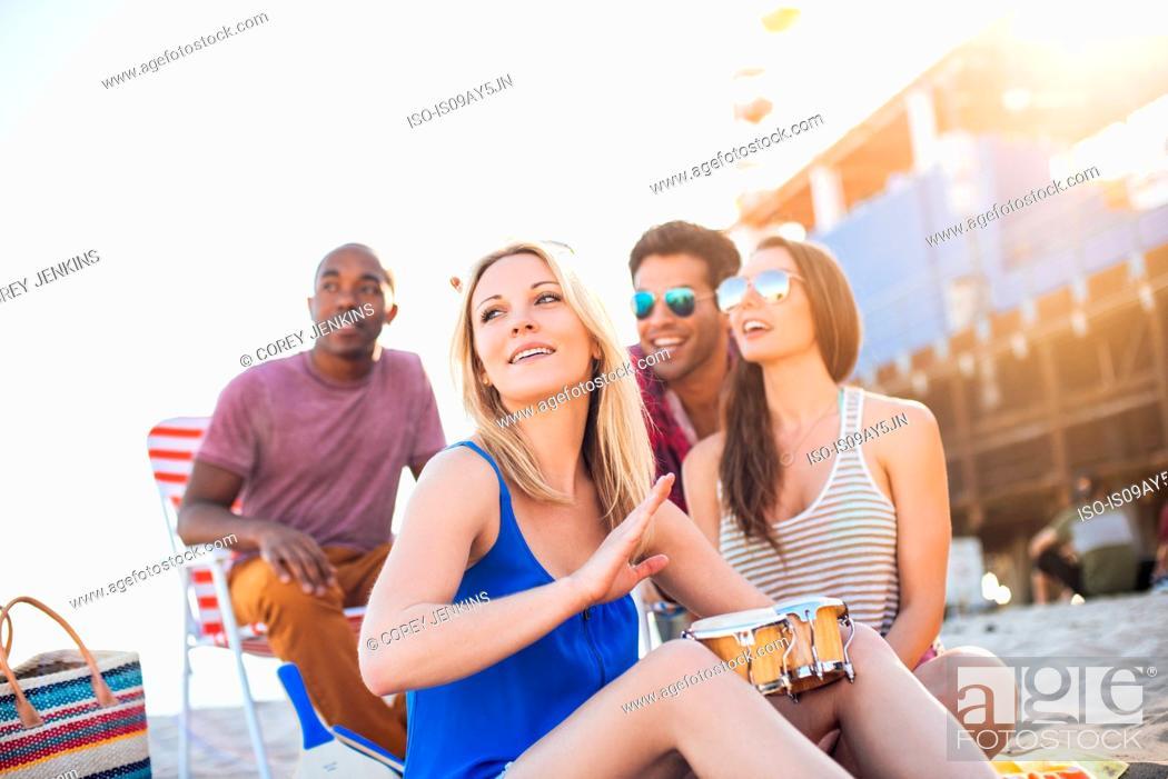 Stock Photo: Young woman with friends bongo drumming on beach, Santa Monica, California, USA.