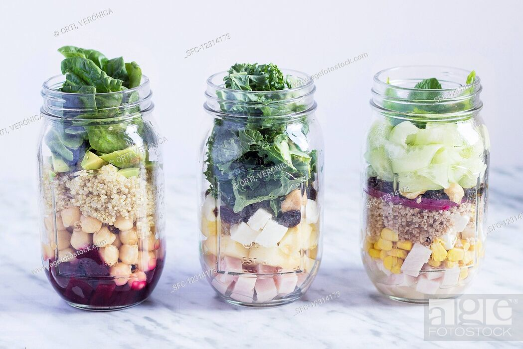 Stock Photo: Different layered salads in glass jars.