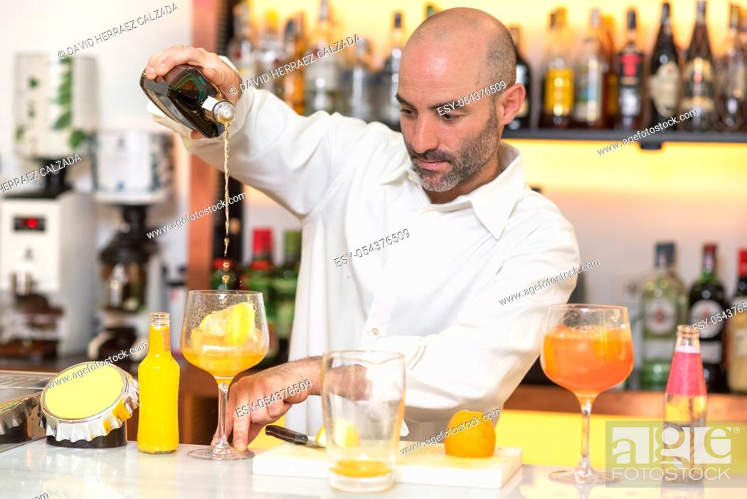 Stock Photo: Expert barman is making cocktail at night club .