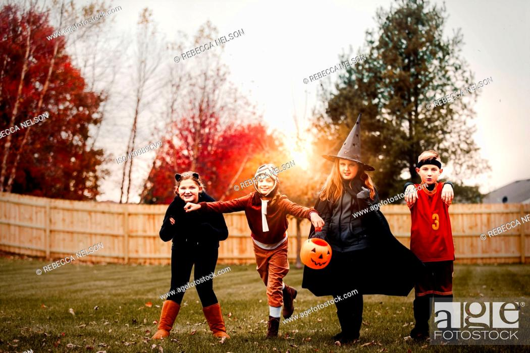 Stock Photo: Portrait of boy and girls posed in halloween costumes in garden at sunset.