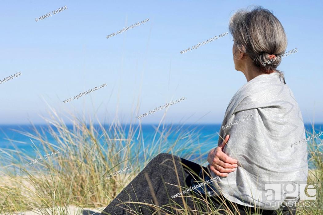 Stock Photo: Senior woman sitting on a beach.