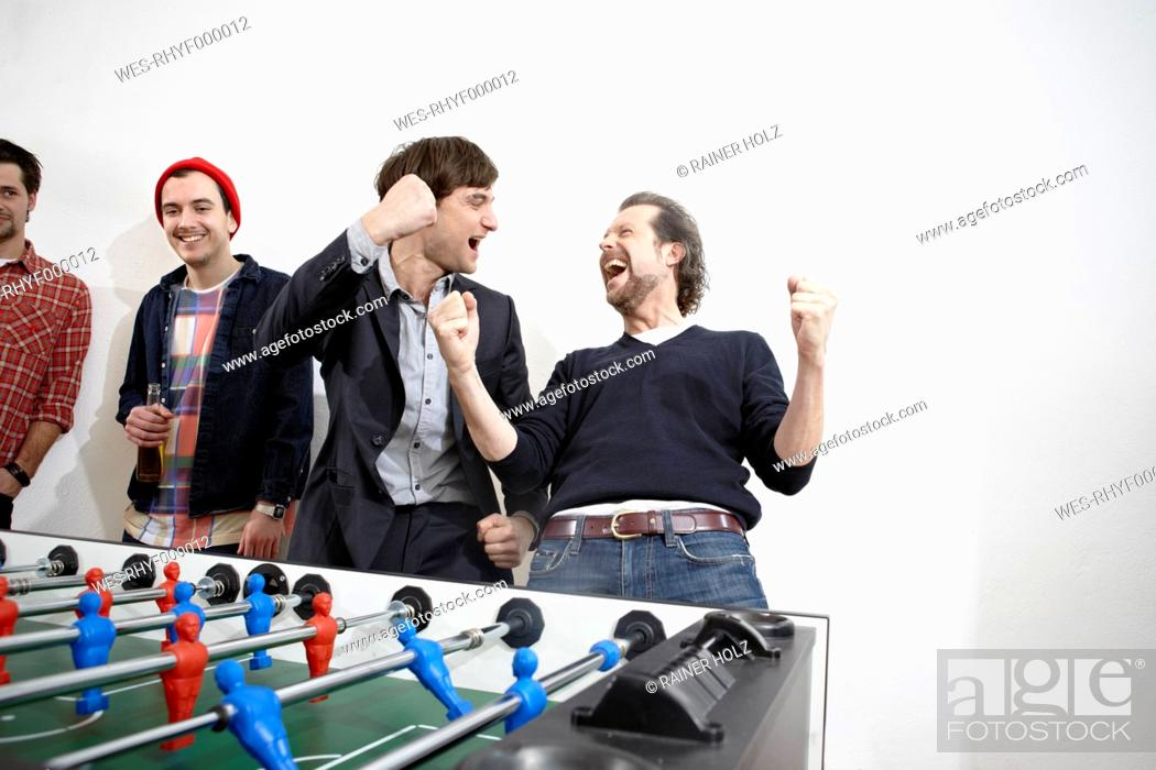 Stock Photo: Germany, Cologne, Men playing table soccer.
