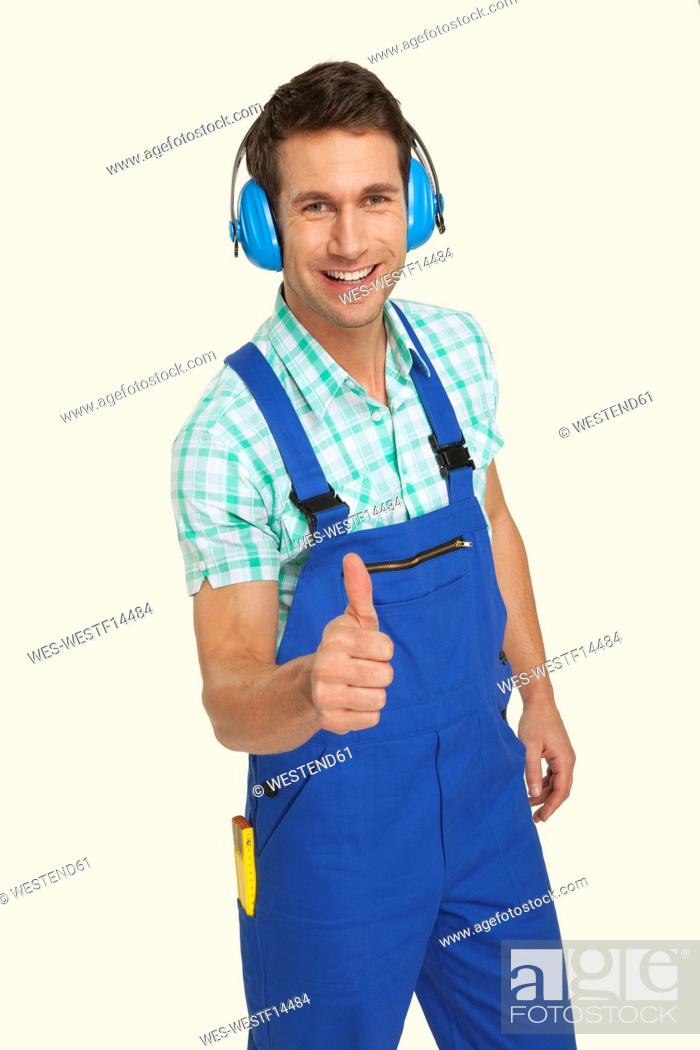 Stock Photo: Man wearing ear muff showing thumbs up sign, smiling, portrait.