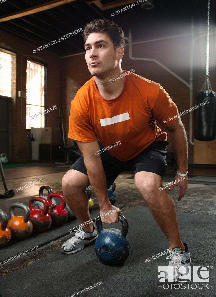 Stock Photo: Bodybuilder lifting kettlebells in gym.