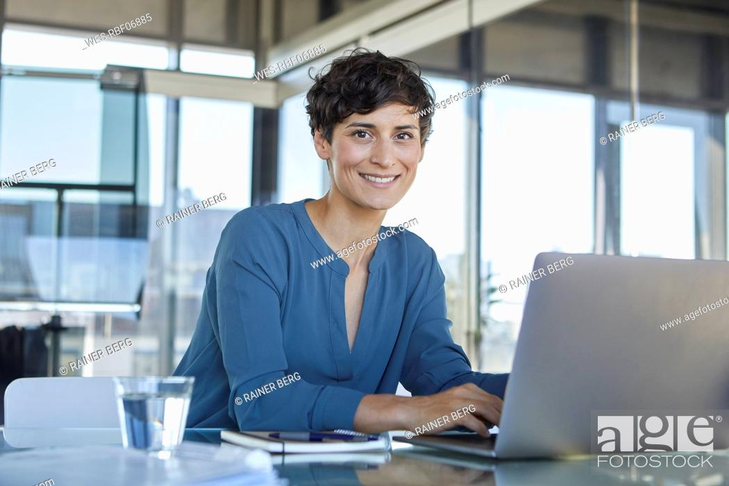Stock Photo: Portrait of confident businesswoman sitting at desk in office with laptop.