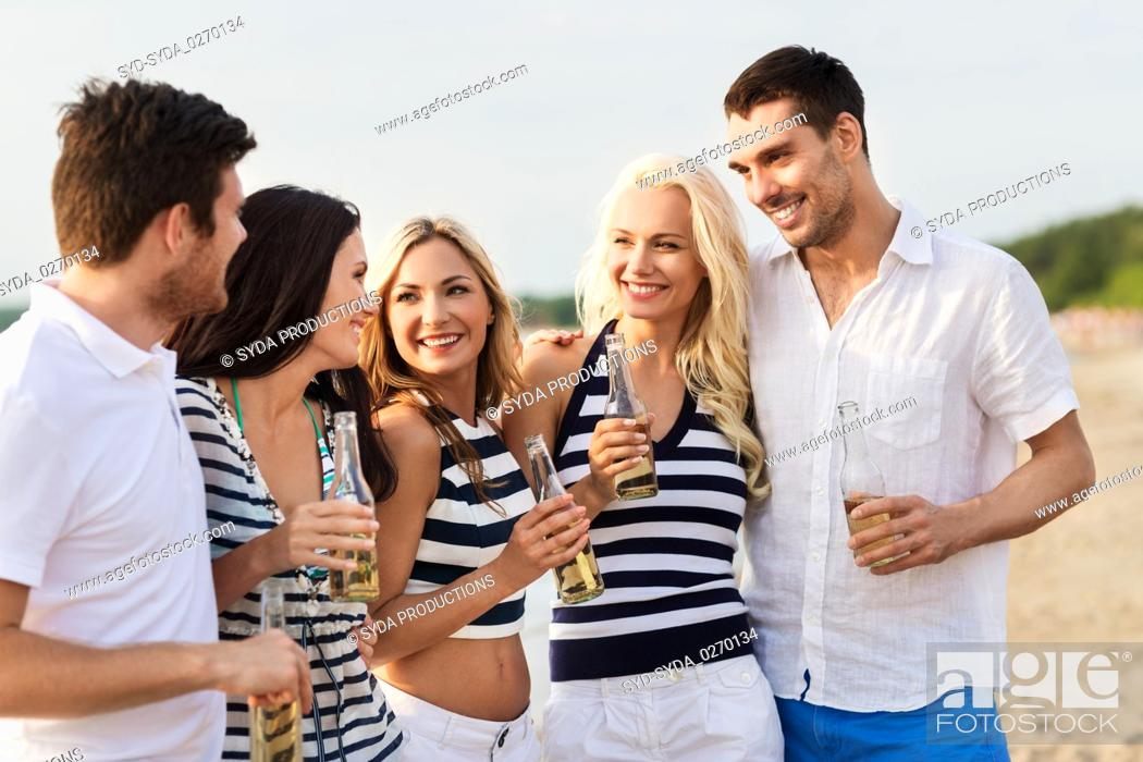 Imagen: happy friends drinking non alcoholic beer on beach.