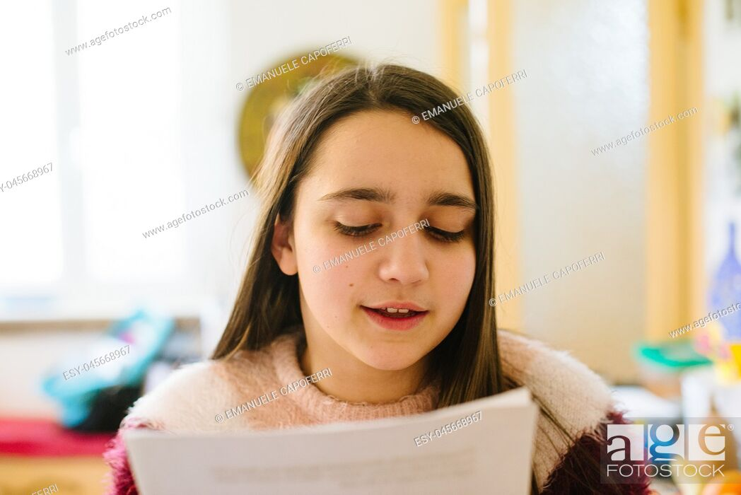 Stock Photo: little girl, teen ager reads the papers she holds in her hand, studies for questioning school-close-up.