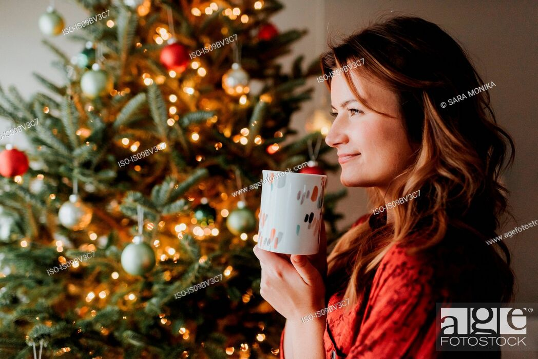 Stock Photo: Woman drinking coffee beside decorated Christmas tree.