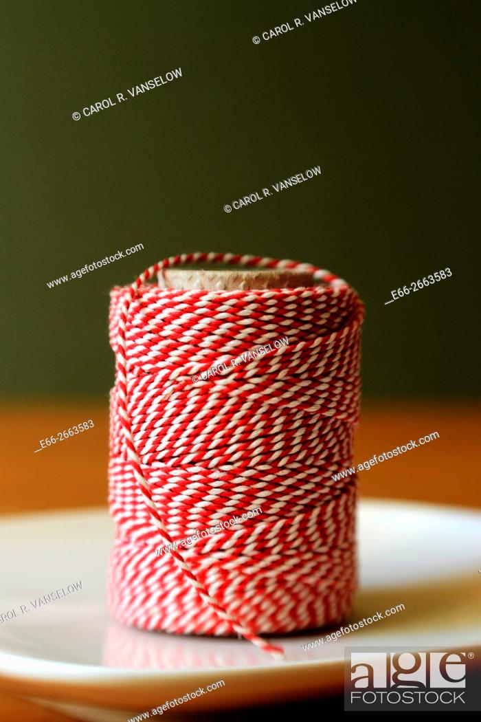 Stock Photo: red and white string used in cooking. Sitting on white plate with dark green background. Shot with LensBaby for selective focus.