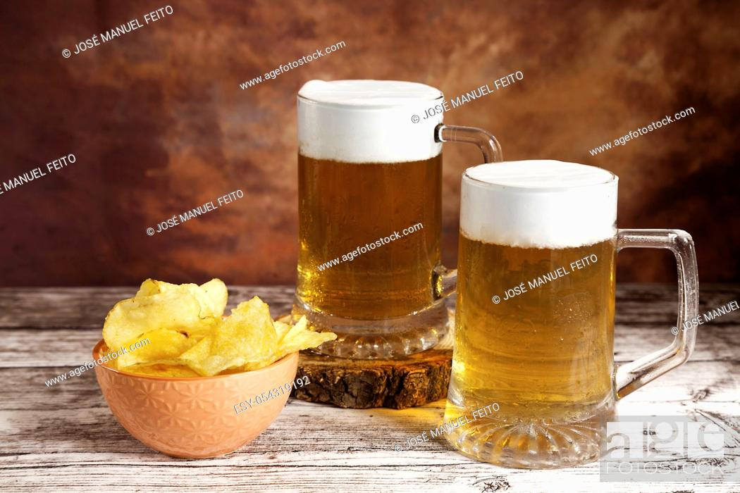 Stock Photo: two beer mugs with foam and bowl of chips on wood table and brown fantasy background.